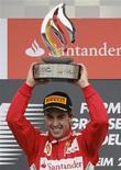 Piloto de F1 Fernando Alonso levanta troféu após vencer o GP da Alemanha no circuito de Hockenheim. O espanhol Fernando Alonso venceu o Grande Prêmio da Alemanha neste domingo, liderando da pole position à bandeirada, e ampliou para 34 pontos a sua liderança no campeonato. 22/07/2012 REUTERS/Wolfgang Rattay