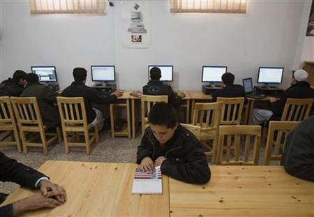 An Afghan boy looks at an educational book as the others use the Internet at the Lincoln U.S. support library in Herat December 13, 2009. REUTERS/Morteza Nikoubazl