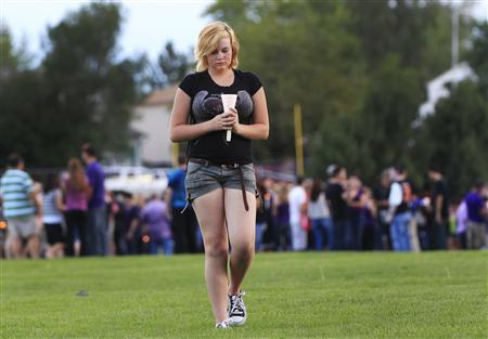 Kieley Tomkus, 14, leaves a memorial honoring AJ Boik, who was killed when a gunman opened fire on moviegoers in Aurora, Colorado July 21, 2012. REUTERS/Shannon Stapleton