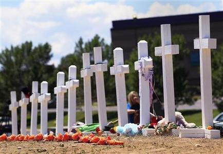 Crosses are seen at a memorial for victims behind the theater where a gunman opened fire on moviegoers in Aurora, Colorado July 22, 2012. President Barack Obama travels to Colorado on Sunday to meet families bereaved after a ''demonic'' gunman went on a shooting rampage at a movie theater in a Denver suburb, killing at least 12 people and wounding 58. REUTERS/Shannon Stapleton