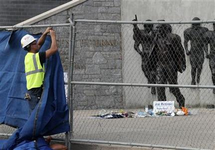 A worker puts up tarps on a temporary fence around the statue of the late Penn State football coach Joe Paterno before removing the statue outside Beaver Stadium in State College, Pennsylvania, July 22, 2012. REUTERS/Craig Houtz