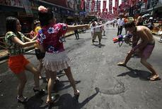 A tourist (R) participates in a water fight with local Thais during the Songkran Festival celebration at Khaosan road in Bangkok April 12, 2012. REUTERS/Chaiwat Subprasom
