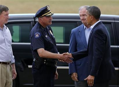 U.S. President Barack Obama shakes hands with Aurora Police Chief Dan Oates (L), next to Mayor of Aurora Steve Hogan (2nd R), after arriving at Buckley Air Force Base in Aurora, Colorado July 22, 2012. Obama travels to Colorado on Sunday to meet families bereaved after a ''demonic'' gunman went on a shooting rampage at a movie theater in a Denver suburb, killing at least 12 people and wounding 58. At left is Colorado Gov. John Hickenlooper. REUTERS/Larry Downing