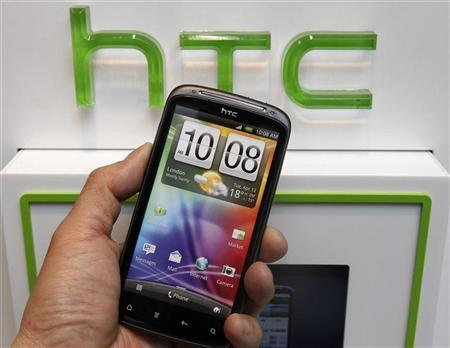 A man poses with a replica of the HTC smartphone inside a mobile phone shop in Taipei April 6, 2012. REUTERS/Shengfa Lin