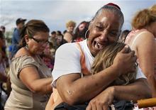 Женщина оплакивает своего 6-летнего племянника, погибшего во время стрельбы в кинотеатре в городке Аврора (штат Колорадо), 27 июля 2012 года. Америка оплакивает жертв пятничной шокирующей стрельбы в кинотеатре в пригороде Денвера, число которых составило 12 человек. REUTERS/Shannon Stapleton
