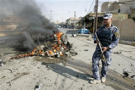 A policeman stands guard at the site of a bomb attack in Kirkuk, 250km (155 miles) north of Baghdad July 23, 2012. REUTERS/Ako Rasheed