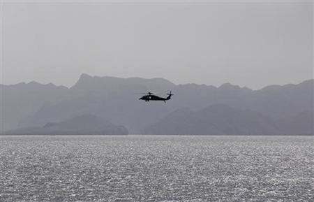 A helicopter from the Nimitz-class aircraft carrier USS Abraham Lincoln (CVN 72) patrols the Arabian Gulf during a transit in the Strait of Hormuz, near the gulf of Oman February 14, 2012. REUTERS/Jumana El Heloueh
