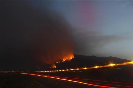 A forest fire is seen on a hill as a fire engine speeds past in the Vilaflor municipality, on the southern part of Spanish Canary Islands of Tenerife, July 18, 2012. REUTERS/Santiago Ferrero