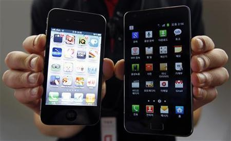 An employee of South Korean mobile carrier KT holds an Apple Inc's iPhone 4 (L) smartphone and a Samsung Electronics' Galaxy S II smartphone as he poses for photographs at a registration desk at KT's headquarters in Seoul, August 25, 2011. REUTERS/Jo Yong-Hak