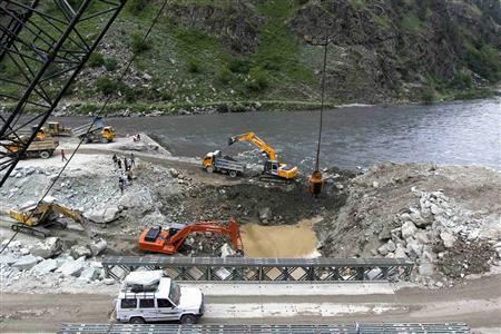 A private vehicle crosses a bridge as excavators are used at the dam site of Kishanganga power project in Gurez, 160 km (99 miles) north of Srinagar June 21, 2012. REUTERS/Fayaz Kabli