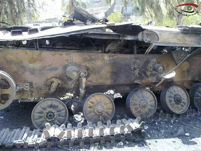 A damaged tank is seen in the suburb of Erbeen in Damascus July 22, 2012. Logo at top right reads, ''Witness of the event''. REUTERS/Shaam News Network/Handout