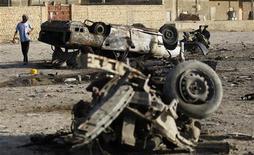 Мальчик стоит около взорвавшегося автомобиля в пригороде Багдада, 23 июля 2012 года. По меньшей мере 89 человек стали жертвами нового витка насилия в Ираке в понедельник, 223 человека получили ранения, сообщили источники в полиции и войсках. REUTERS/Mohammed Ameen