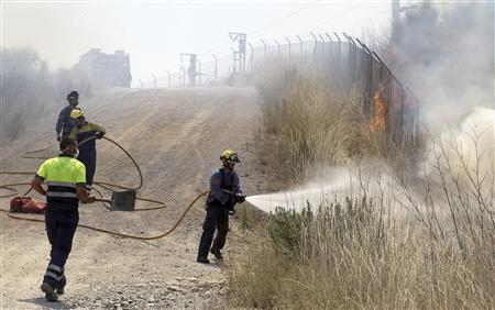 Firefighters work to put out a fire on the TGV (high speed train) Barcelona-Perpignan line in Hostalets de Llers, Spanish province of Girona, July 23, 2012. REUTERS/Jordi Ribot