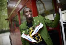 Velocista jamaicano Usain Bolt posa com seu uniforme oficial para os Jogos Olímpicos durante ensaio fotográfico ao lado de um ônibus tradicional de Londres. 01/06/2012 REUTERS/Dylan Martinez