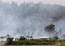 Farmers try to put out a fire near Llers, in the Spanish province of Girona, July 23, 2012. REUTERS/Albert Gea