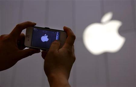 A man shows a photograph he took on his iPhone of an Apple store in Beijing June 6, 2012. REUTERS/David Gray