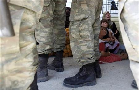 A Syrian refugee woman seen behind Turkish soldiers with her children shouts after fleeing from a refugee camp named ''Container City'' on the Turkish-Syrian border in Oncupinar in Kilis province, southern Turkey July 22, 2012. REUTERS/Umit Bektas