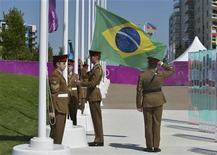 A bandeira brasileira é hasteada enquanto membros do delegação Olímpica brasileira são recebidos durante uma cerimônia na Vila Olímpica, em Londres. 23/07/2012 REUTERS/Pool