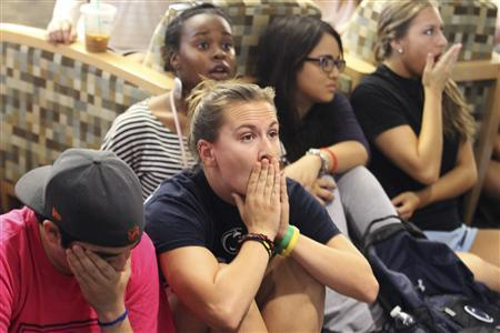 Penn State University students Andrew Hanselman, (L), and Maddy Pryor, (2nd L), react while watching a live broadcast of the announcement of the NCAA penalties and sanctions at the HUB-Robeson Center on the Penn State campus in State College, PA July 23, 2012. REUTERS/Craig Houtz
