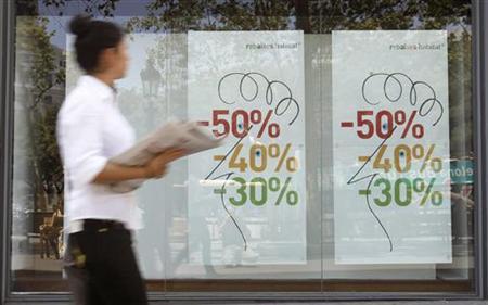A woman walks past sales banners on a shop window in Barcelona July 15, 2012. REUTERS/Albert Gea