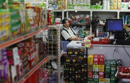 Lee Jin-taek (61) watches television at his general store in Seoul July 16, 2012. REUTERS/Kim Hong-Ji