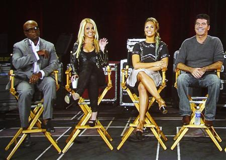 Judges from the reality series ''The X Factor'' (L-R) L.A. Reid, Britney Spears, Demi Lovato and Simon Cowell are pictured on a video screen via satellite from Miami, Florida, during a panel discussion at the Fox television network portion of the Television Critics Association Summer press tour in Beverly Hills, California July 23, 2012. REUTERS/Fred Prouser
