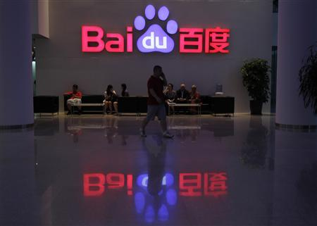A employee uses his mobile phone as he walks past the company logo of Baidu at its headquarters in Beijing, in this August 5, 2010 file photograph. REUTERS/Barry Huang/Files