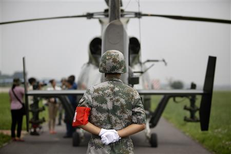 A soldier stands guard behind a Z-9WZ military helicopter designed and manufactured by China during a media visit at the military base of Chinese People's Liberation Army (PLA) Army Aviation 4th Helicopter Regiment, on the outskirts of Beijing, July 24, 2012, ahead of Army Day on August 1. REUTERS/Jason Lee