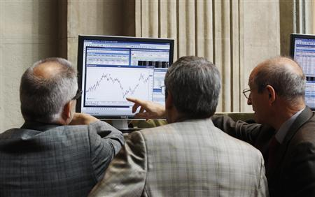 Traders look at a computer screen at the Madrid Bourse July 24, 2012. REUTERS/Andrea Comas