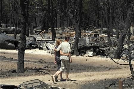 A couple walks along Les Pedres campsite after a fire burnt it in Capmany, in the province of Girona, July 23, 2012. REUTERS/Joan Castro