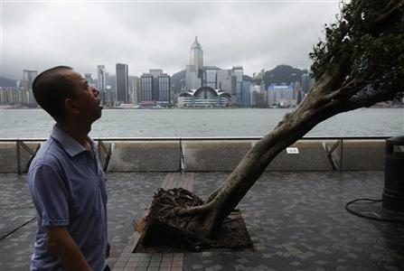 A man reacts while walking past an uprooted tree after Typhoon Vicente hit Hong Kong July 24, 2012. REUTERS/Tyrone Siu