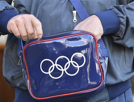 An official carries a bag with an Olympic rings design on it in the Athletes Village at Olympic Park in Stratford in east London July 23, 2012. REUTERS/Toby Melville