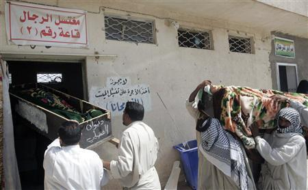 Relatives of victims killed in one of Monday's bomb attacks, carry their coffins before a burial ceremony at a cemetery in Najaf 160 km (99 miles) south of Baghdad July 24, 2012. REUTERS/Ali Abu Shish