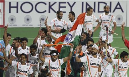 Indian players hold India's national flags as they take a victory lap after their win over France in the London 2012 Olympic Games men's field hockey final qualifying match in New Delhi February 26, 2012. REUTERS/B Mathur