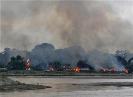 Flames erupt from huts built on the banks of river Gourang during violence near Kokrajhar town in Assam July 24, 2012. REUTERS/Stringer