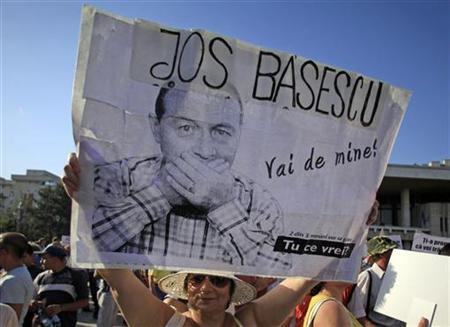 A woman holds a sign that reads ''Down Basescu'' during a rally promoting the impeachment of suspended President Traian Basescu in Craiova, 248 km (154 miles) west of Bucharest, July 20, 2012. REUTERS/Radu Sigheti