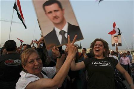 Jordanians and Syrians living in Jordan hold pictures of Syria's President Bashar al-Assad and shout slogans against the Syrian Revolution during a demonstration in support of al-Assad, as Syrian refugees protest against al-Assad near the Syrian embassy in Amman July 19, 2012. REUTERS/Muhammad Hamed