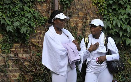 Venus Williams of the U.S. (L) and sister Serena talk following a practice session at Wimbledon in London June 18, 2011. REUTERS/Toby Melville