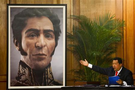 Venezuelan President Hugo Chavez shows an image of independence hero Simon Bolivar during a ceremony to mark his birthday in Caracas July 24, 2012. REUTERS/Carlos Garcia Rawlins