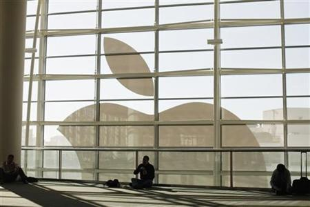 Attendees sit in front of an Apple logo during the Apple Worldwide Developers Conference 2012 in San Francisco, California June 11, 2012. REUTERS/Stephen Lam/Files