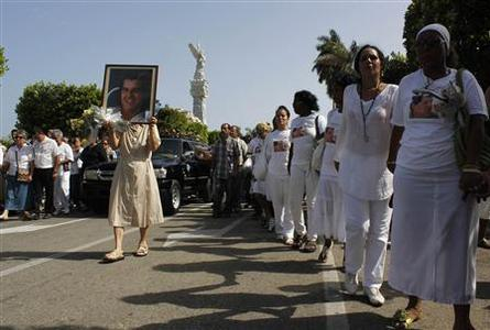Members of the 'Ladies in White' opposition group march beside the funeral procession of Oswaldo Paya, one of Cuba's best-known dissidents, in Havana July 24, 2012. REUTERS/Stringer