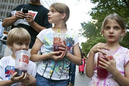 Benjamin, 8, Alana, 10, and Sara Lesczynski (L-R), 8, of New York, hold ''Big Gulp'' drinks while protesting the proposed ''soda-ban,'' that New York City Mayor Michael R. Bloomberg has suggested, outside City Hall in New York July 9, 2012. REUTERS/Andrew Burton