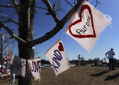 Signs drawn on fabric are seen hanging from a tree at a memorial for victims behind the theater where a gunman opened fire on moviegoers in Aurora, Colorado July 24, 2012. REUTERS/Shannon Stapleton