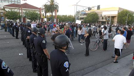 Police officers from Orange County in riot gear walk towards protesters attempting to occupy the corner of Anaheim Blvd. and Broadway to demonstrate against recent police shootings in Anaheim, California July 24, 2012. REUTERS-Alex Gallardo