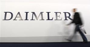 Мужчина проходит мимо логотипа Daimler AG в Берлине, 4 апреля 2012 года. Прибыль немецкого автопроизводителя Daimler снизилась во втором квартале, но оказалась лучше рыночных ожиданий, позволив компании подтвердить годовой прогноз. REUTERS/Fabrizio Bensch