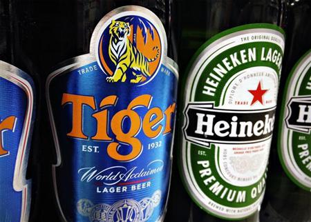 Bottles of Tiger and Heineken beers are pictured on the shelf of a grocery store in Singapore July 20, 2012. REUTERS/Tim Chong
