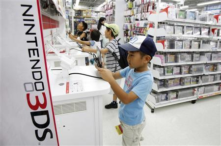 Boys try out Nintendo's 3DS game software at an electronic store in Tokyo July 25, 2012. REUTERS/Yuriko Nakao