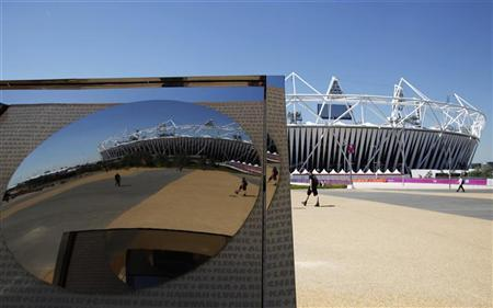 A man walks past the Olympic stadium at the Olympic Park in Stratford, the location of the London 2012 Olympic Games, in east London July 24, 2012. REUTERS/Toru Hanai