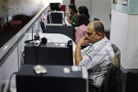Office workers sit in front of their workstations on the floor of an outsourcing centre in Bangalore, February 29, 2012. REUTERS/Vivek Prakash/Files