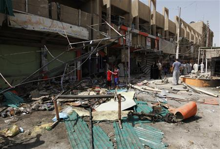 Residents stand amid debris and twisted metal near shops damaged by a car bomb attack that occurred late on Monday in east of Baghdad July 24, 2012. REUTERS/HAYDER KHADIM